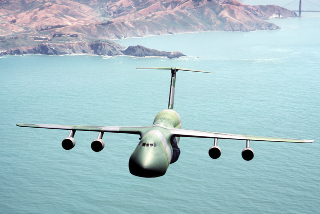 An air-to-air right side view of a C-5 Galaxy aircraft, as it flies over San Francisco Bay