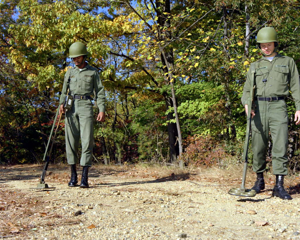 Two soldiers use mine detectors fitted with microcomputer circuitry to locate land mines. The new circuitry gives the detectors improved performance in desert soils. The AN/PSS-11 metallic detector is on the left and the AN/PRS-8 metallic/non-metallic detector is on the right