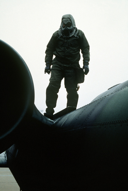 A maintenance specialist, wearing chemical warfare gear, stands on top of an A-10 Thunderbolt II aircraft during Condor CRTE '82, a combat rescue exercise aimed at giving reservists battlefield experience