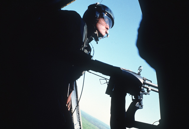 """A pararescue specialist aims his M-60 machine gun out the door of an HH-3E helicopter as rescue forces retrieve a """"survivor"""" during Condor CRTE '82, a combat rescue exercise designed to give reservists battlefield experience"""