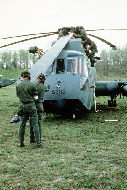 "Air Force Reserve mechanics replace the main rotor blade of an HH-3E helicopter ""shot down"" during Condor CRTE '82, a combat rescue exercise aimed at giving reservists battlefield experience"