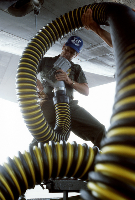 Air Force Reserve STAFF Sergeant Robert Beaulieu prepares to attach a flushing hose to a C-141 Starlifter aircraft. He is participating in PATRIOT PORT '83, a reserve exercise in which Air Force Reserve personnel from the 57th and 85th Aerial Port Squadrons (APS), Hanscom Air Force Base, Massachusetts take over the duties of the 437th APS