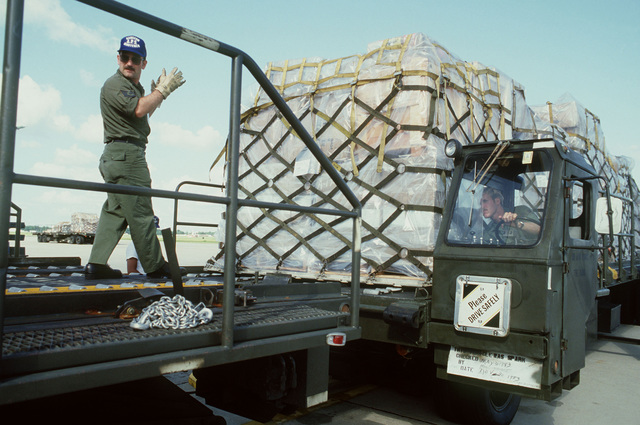 Air Force Reserve Technical Sergeant Timothy N. Brienza guides a pallet of cargo onto the loading ramp of a C-141 Starlifter aircraft. He is participating in PATRIOT PORT '83, a reserve exercise in which reserve personnel from the 57th and 85th Aerial Port Squadrons (APS), Hanscom Air Force Base, Massachusetts, take over the duties of the 437th APS