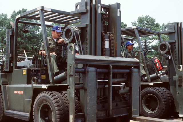 Air Force Reservist STAFF Sergeant George Connolly and SENIOR AIRMAN Maxine Walker familiarize themselves with a pair of forklifts. They are participating in PATRIOT PORT '83, a reserve exercise in which reserve personnel from the 57th and 85th Aerial Port Squadrons (APS), Hanscom Air Force Base, Massachusetts, take over the duties of the 437th APS