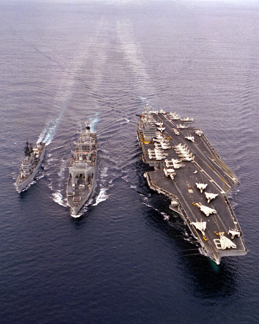 An aerial bow view of the nuclear-powered aircraft carrier USS DWIGHT D. EISENHOWER (CVN-69), right, conducting underway replenishment with the Ashtabula Class oiler USS CALOOSAHATCHEE (AO-98), center, during Exercise Bright Star '83. The Forrest Sherman Class destroyer USS MANLEY (DD-940) is underway to the left