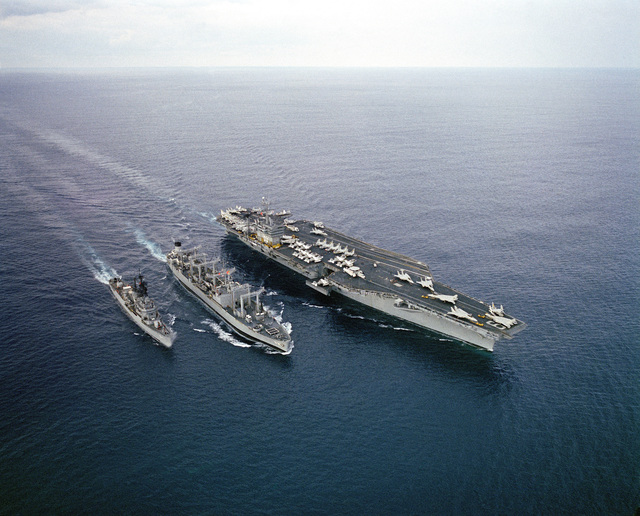 An aerial starboard bow view of the nuclear-powered aircraft carrier USS DWIGHT D. EISENHOWER (CVN 69), right, conducting underway replenishment with the Ashtabula class oiler USS CALOOSAHATCHEE (AO 98), center, during Exercise BRIGHT STAR '83. The Forrest Sherman class destroyer USS MANLEY (DD 940) is underway to the left