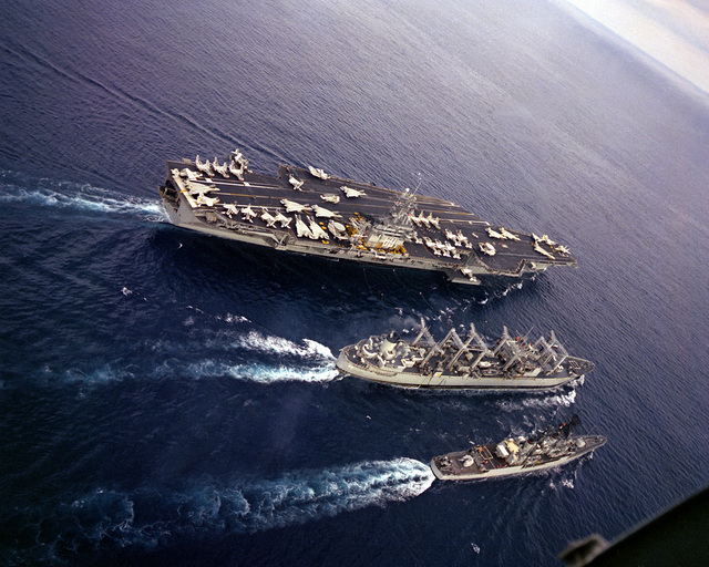 An aerial starboard quarter view of the nuclear-powered aircraft carrier USS DWIGHT D. EISENHOWER (CVN-69), right, conducting underway replenishment with the Ashtabula Class oiler USS CALOOSAHATCHEE (AO-98), center, during Exercise Bright Star '83. The Forrest Sherman Class destroyer USS MANLEY (DD-940) is underway to the bottom right