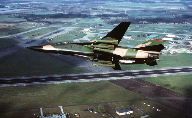 An air-to-air left underside view of an F-111 aircraft flown by the 48th Tactical Fighter Wing, RAF Lakenheath. Mounted on the F-111's wing pylons are four Paveway laser-guided bombs