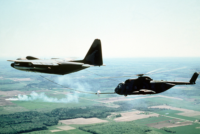 An HC-130 Hercules aircraft refuels an HH-3E helicopter during Condor CRTE '82, a combat rescue exercise aimed at giving reservists battlefield experience