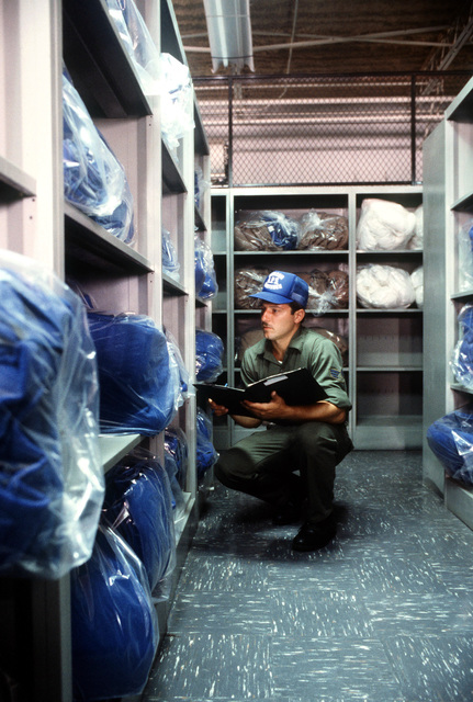 SENIOR AIRMAN Richard Chartienitz, assigned to the 85th Aerial Port Squadron (AFRES), Hanscom Air Force Base, Massachusetts, checks inventory in the fleet service supply area. The 85th APS is taking over the duties of the 437th APS during the reserve exercise PATRIOT PORT `83
