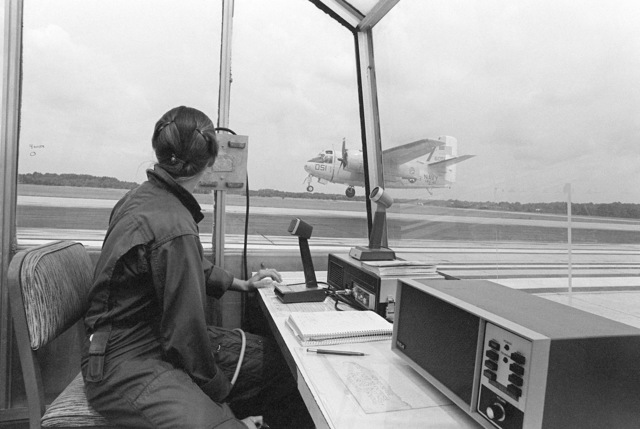 Lieutenant Junior Grade (LTJG) Leslie Provow of Fleet Logistics Support Squadron 40 (VRC-40) watches from the air operations control center as a C-1A Trader aircraft makes touch and go landings. LTJG Provow is the landing signal officer (LSO)