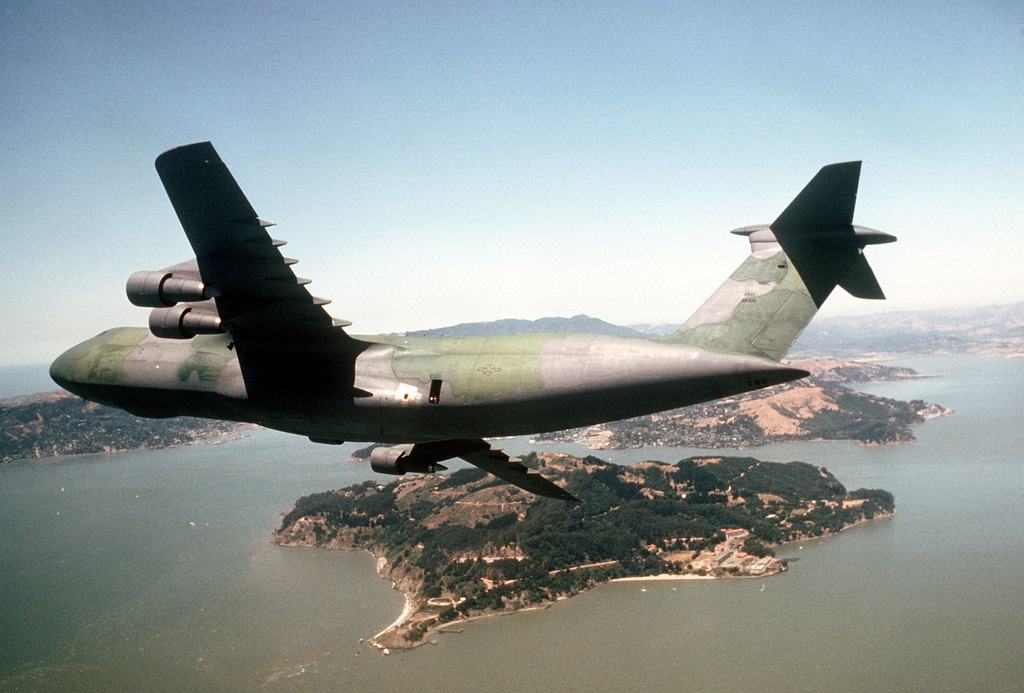 An air-to-air front view of a C-5 Galaxy aircraft over San Francisco Bay. The C-5, one of the first to be painted in a camouflage pattern, is en route to Cairo, Egypt