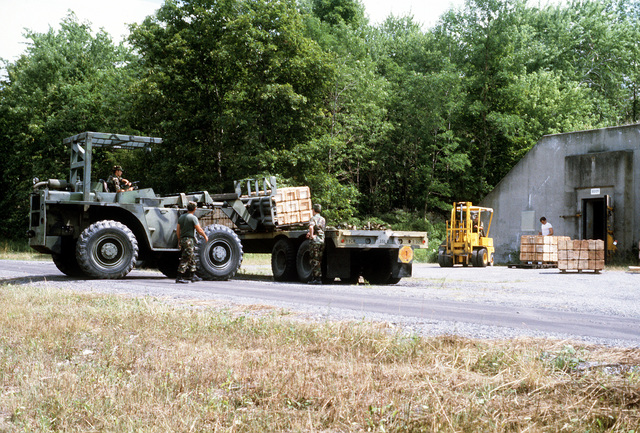 Army reservists of the 351st Ordnance Co. from Romney, W.V., offload a flatbed trailer using a 10,000-lb. rough-terrain forklift. The reservists are assisting the Directorate for Supply by re-warehousing igloos of category II ammunition (demolition blocks) during their annual training at the Seneca Army Depot