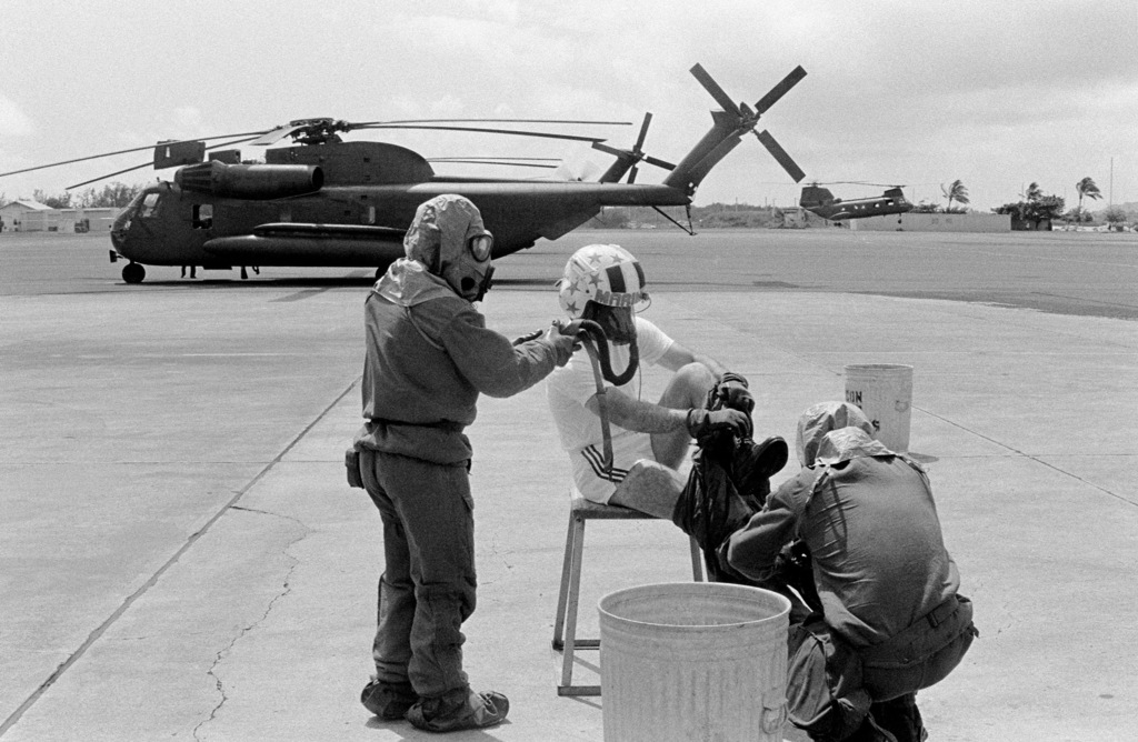 Lieutenant Colonel Thomas W. Holden, commanding officer of Marine Medium Helicopter Squadron 262 (HMM-262), is helped by members of the squadron's decontamination team as he removes his flight suit during a combat readiness evaluation exercise. The team is wearing nuclear-biological-chemical (NBC) gear. A CH-53 Sea Stallion and a CH-46 Sea Knight helicopter are visible