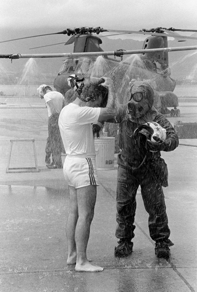 Lieutenant Colonel Thomas W. Holden, commanding officer of Marine Medium Helicopter Squadron 262 (HMM-262), is assisted by a member of the squadron's decontamination team as he stands under a decontamination shower during a combat readiness evaluation exercise. The team member is in nuclear-biological-chemical (NBC) gear. A CH-46 Sea Knight helicopter is visible