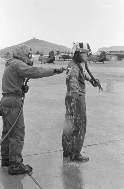 Lieutenant Colonel Thomas W. Holden, commanding officer of Marine Medium Helicopter Squadron 262 (HMM-262), undergoes decontamination procedures with the aid of Private First Class (PFC) Lipps during a combat readiness evaluation exercise. PFC Lipps is wearing nuclear-biological-chemical (NBC) gear. Visible in the background are two CH-46 Sea Knight helicopters