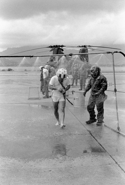 Lieutenant Colonel Thomas W. Holden, commanding officer of Marine Medium Helicopter Squadron 262 (HMM-262), walks through a decontamination shower as members of the squadron's decontamination team look on during a combat readiness evaluation exercise. The team is wearing nuclear-biological-chemical (NBC) gear. A CH-46 Sea Knight helicopter is visible