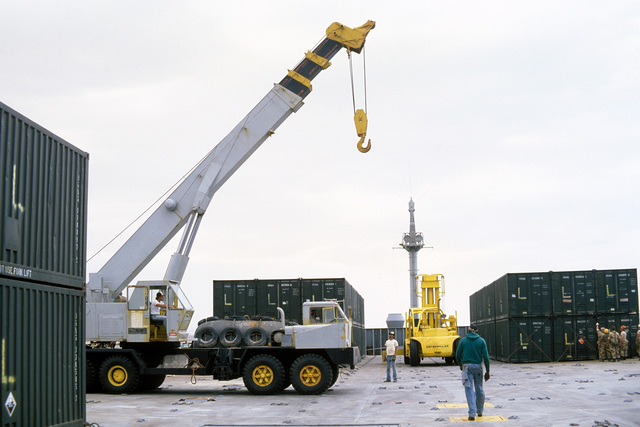 Civilian workers use a mobile crane to offload US Marine Corps equipment from a container ship SS LYRA during Exercise EASTERN WIND '83, the amphibious landing phase of Exercise BRIGHT STAR '83