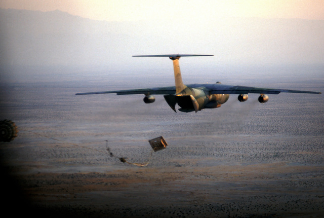 An air-to-air rear view of a C-141B Starlifter aircraft para-dropping a cargo pallet during a practice mission for VOLANT RODEO 83. The C-141B is painted in the new Euro-1 camouflage paint scheme
