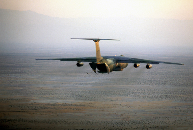 An air-to-air rear view of a C-141B Starlifter aircraft preparing to para-drop a cargo pallet during a practice mission for VOLANT RODEO 83. The C-141B is painted in the new Euro-1 camouflage paint scheme