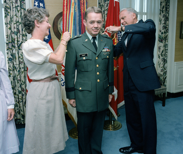 Secretary of the Army John O. Marsh Jr. and Peggy Knapp pin new stars onto the shoulders of Brigadier General (BGEN) John W. Knapp, US Army Reserve, during a ceremony in Marsh's office at the Pentagon