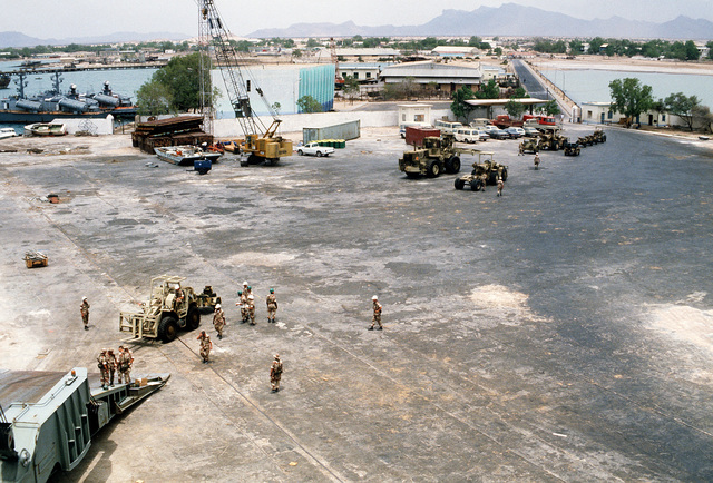 U.S. Marine Corps equipment is offloaded from the container ship SS LYRA during Exercise Eastern Wind '83, the amphibious landing phase of Exercise Bright Star '83. Two Somalian navy (ex-Soviet) Osa II Class fast attack craft (missile) are visible in the upper left
