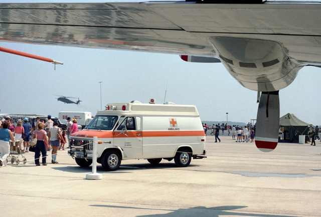 A Navy ambulance stops near a P-3 Orion aircraft on public display during the open house airshow Expo '83. The ambulance has arrived to treat a visitor that collapsed from heat prostration during the airshow