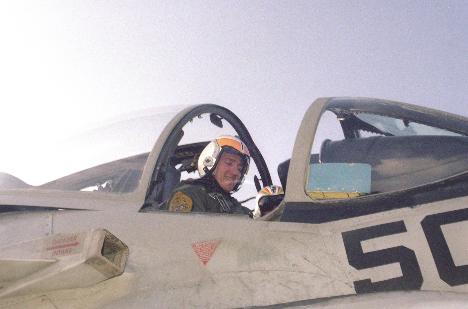 Secretary of the Navy John F. Lehman Jr. straps himself into an Attack Squadron 65 (VA-65) A-6E intruder aircraft being readied for launch on the deckof the nuclear-powered aircraft carrier USS DWIGHT D. EISENHOWER (CVN-69)