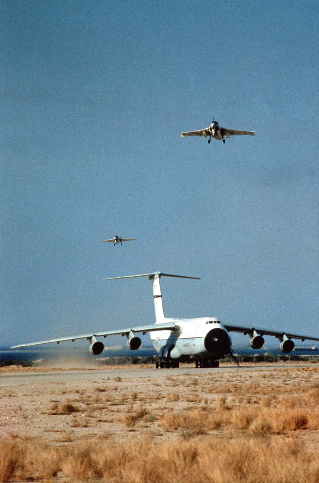 A right front view of a C-5A Galaxy aircraft in use during the joint Exercise BRIGHT STAR '83. Two A-6 Intruder aircraft fly overhead