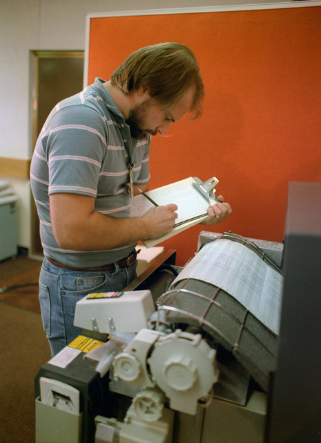 A technician monitors a computer printout while testing the electrical circuits of an MGM-118 Peacekeeper (formerly MX) intercontinental ballistic missile control guidance system