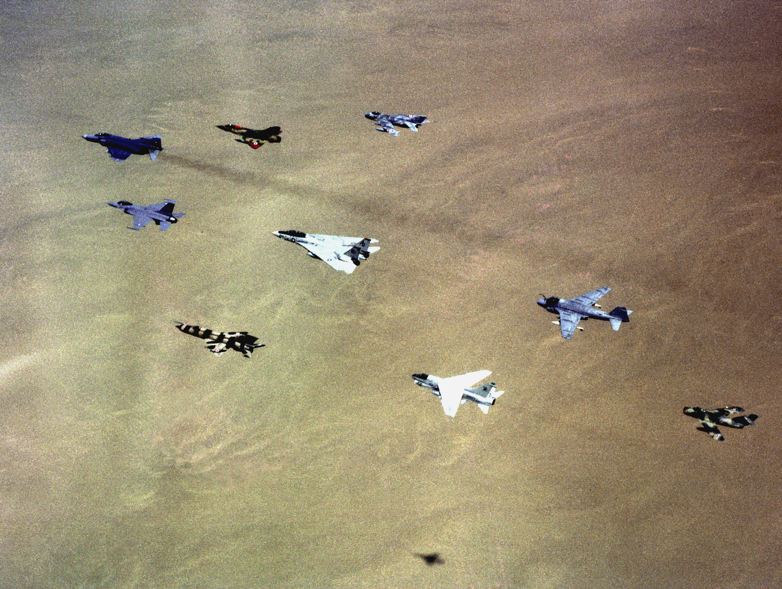 An air-to-air view of a joint formation of aircraft participating in the multi-national exercise Bright Star '83. The aircraft are, clockwise from the top: Egyptian air force MiG-19 Farmer, U.S. Navy A-6 Intruder, Egyptian air force MiG-17 Fresco, U.S. Navy A-7 Corsair II, Egyptian air force MiG-21 Fishbed, Egyptian air force F-16 Fighting Falcon, Egyptian air force F-4 Phantom II, Egyptian air force Mirage 2000, and a U.S. Navy F-14 Tomcat in the center