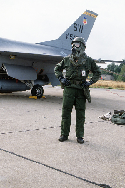 A member of the 19th Tactical Fighter Squadron, wearing an M-17 chemical-biological field mask, participates in a nuclear biological chemical (NBC) warfare exercise during CORNET GAUNTLET '83. Parked behind him is an F-16 Fighting Falcon aircraft