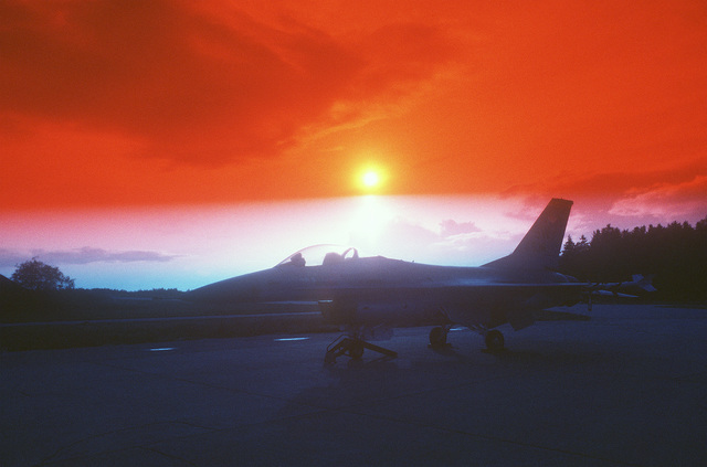 A right front view (taken at sunset) of an F-16 Fighting Falcon aircraft parked on the flight line during Exercise CORNET GAUNTLET '83