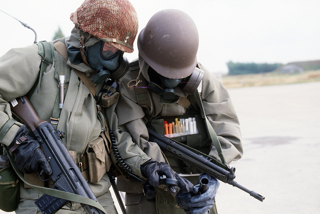 Norwegian soldiers, wearing British-designed NBC S6 respirators and armed with G3 7.62 mm rifles, participate in Exercise CORNET GAUNTLET '83