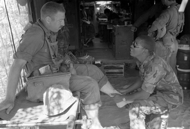 SPECIALIST Sixth Class Dale Larry, a medical aidman with the Medical Platoon, 3/37 Armor, administers first-aid to STAFF Sergeant Steve Colson while on manuvers at the National Training Center