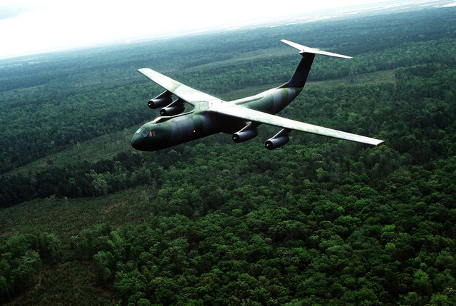 An air-to-air left front view of a C-141 Starlifter aircraft in camouflage paint scheme, from the 437th Military Airlift Wing