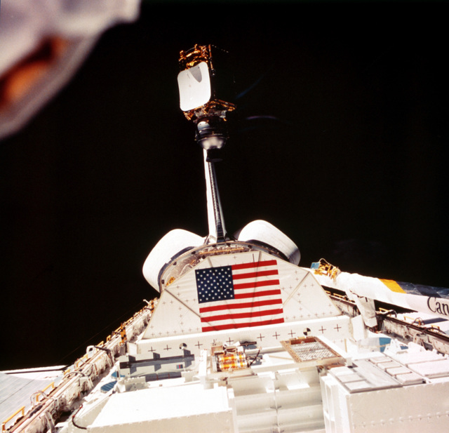 The Indian National Satellite (INSAT), attached to a payload assist module, emerges from the cargo bay of the Space Shuttle Orbiter Challenger (STS-8). Also visible are the Payload Flight Test Article (PFTA), displaying the American flag, and the Canadian-built Remote Manipulator System (RMS), on the right