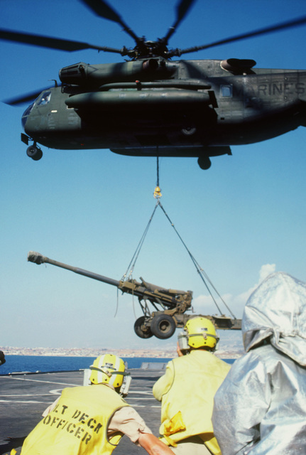 A left side view of a Marine Corps CH-53E Super Stallion helicopter lifting an M198 155 mm howitzer from the flight deck of the amphibious transport dock USS AUSTIN (LPD 4). The AUSTIN is deployed off the coast of Beirut, Lebanon in support of the United States contingent of the multinational peacekeeping force