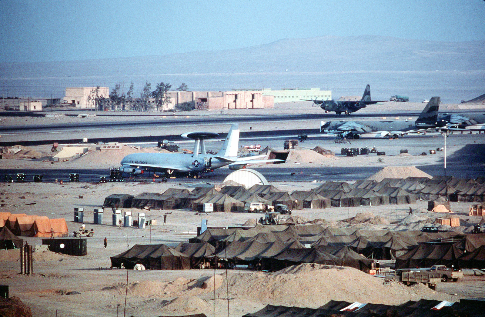 An Air Force C-130 Hercules aircraft lands at an aircraft staging area known as Cairo West during the multinational exercise Bright Star '83. An E-3A Sentry airborne warning and control system (AVACS) aircraft and a B-52 Stratofortress are being serviced in the foreground