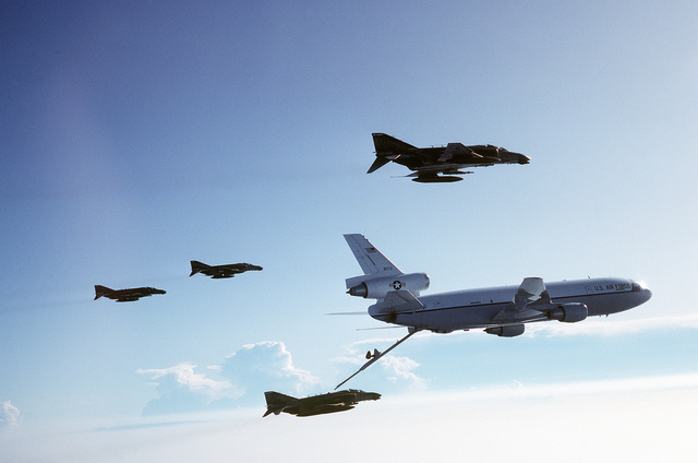 An air-to-air right side view of an F-4 Phantom II aircraft from the 457th Tactical Fighter Squadron (Air Force Reserve) being refueled by a KC-10 Extender aircraft. The other F-4s are visible