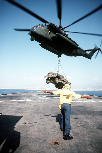 Aviation Boatswain's Mate 2nd Class (ABH-2) Leroy V. Young directs a Marine CH-53E Sea Stallion helicopter lifting a 2 1/2-ton truck from the flight deck of the amphibious transport dock USS AUSTIN (LPD-4). The truck will be taken ashore to be used by U.S. Marines assigned to a multinational peacekeeping force in Beirut, Lebanon