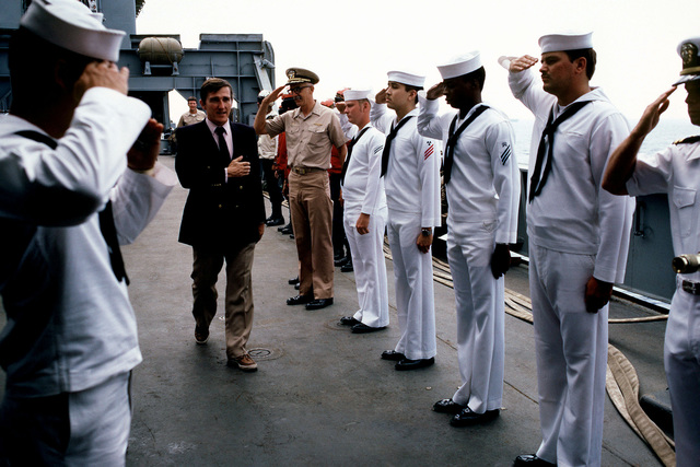 Secretary of the Navy John F. Lehman Jr. passes between sideboys aboard the amphibious cargo ship USS EL PASO (LKA 117) operating off the coast of Lebanon. Lehman is touring the American contingent of the multinational peacekeeping force in Beirut, Lebanon