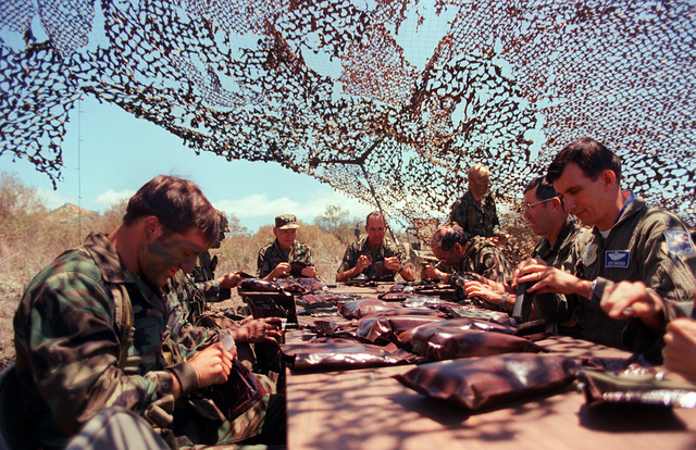 LT. GEN. James M. Lee (left center), Commander, WESTCOM, sits with MAJ. GEN. William H. Schneider, Commander, 25th Inf. Div., and members of the Combat Support Company, 1ST Bn., 35th Inf., 25th Inf. Div., as they dine on experimental MRE (Meal Ready-to-Eat) rations