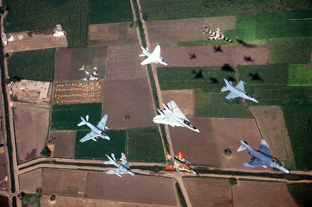 An air-to-air top view of U.S. and Egyptian aircraft in formation during the joint exercise Bright Star '83. The aircraft (clockwise from bottom right) are an Egyptian F-4 Phantom II, Mirage 2000, MiG-17, American A-6 Intruder, Egyptian MiG-15, American A-7 Corsair II, Egyptian MiG-21, Egyptian F-16B Fighting Falcon, and an American F-14 Tomcat, center