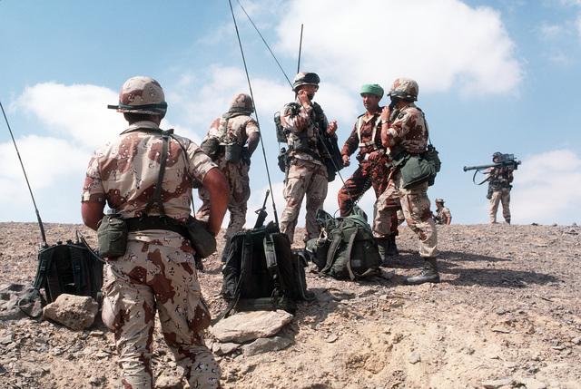 An Egyptian soldier observes American soldiers communicating with helicopter pilots, as an air assault takes place during the joint Exercise Bright Star '83. The soldier in the background is armed with a Stinger anti-aircraft guided missile system