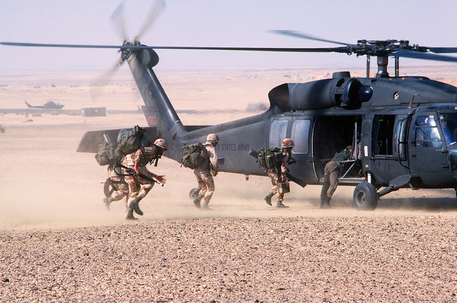 Members of the 101st Airborne Division move toward a UH-60 Black Hawk (Blackhawk) helicopter as an air assault takes place during the joint Exercise Bright Star '83