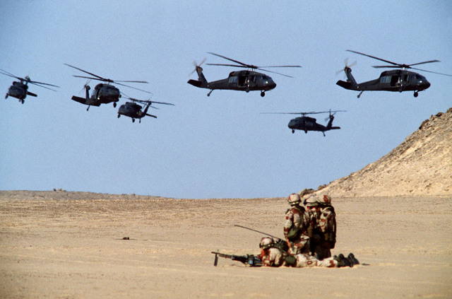 Six UH-60 Black Hawk (Blackhawk) helicopters of the 101st Airborne Division fly above a group of soldiers in the desert, as an air assault takes place during the joint Exercise Bright Star '83