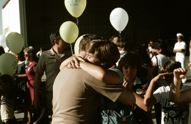 A member of Light Attack Squadron 27 (VA-27) greet his wife and family upon his return to the squadron's home base