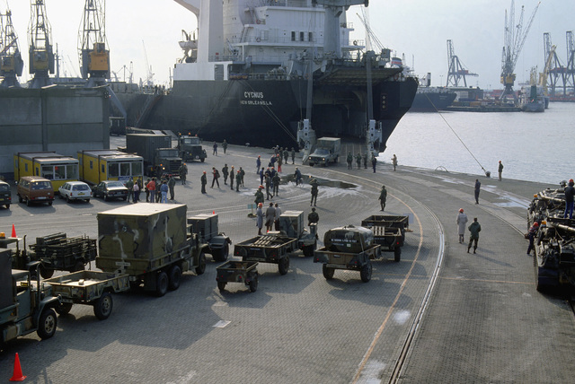 Army vehicles and trailers are parked on the dock after being offloaded from the chartered Military Sealift Command vehicle cargo ship USNS CYGNUS (T-AK 113). The vehicles will beused in support of Exercise REFORGER '83