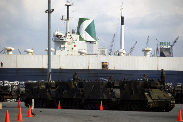 Four M577 command post armored personnel carriers parked on the dock after being offloaded from the Military Sealift Command vehicle cargo ship USNS CYGNUS (T-AK 113). The vehicles will be used in support of Exercise REFORGER '83
